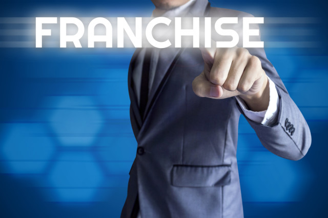 Business man touch modern interface for Franchise concept on blue background.
