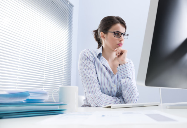 Pensive businesswoman staring at computer screen and touching her chin.