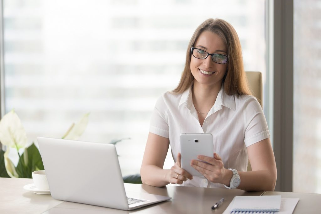 Portrait of happy businesswoman at desk holding tablet in hands, looking at camera. Female entrepreneur using phablet in office. Smiling woman inspects electronic documentation, digital office work