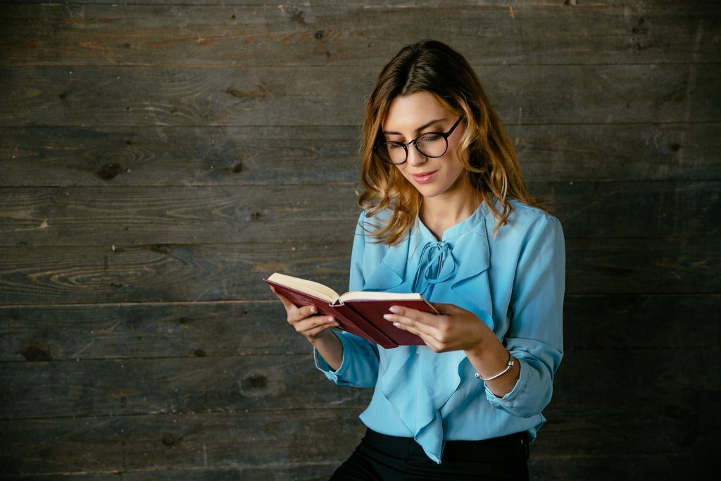 Gorgeous beautiful clever woman in eyeglasses reading interesting book, looks pensive. Dressed in fashionable blouse.