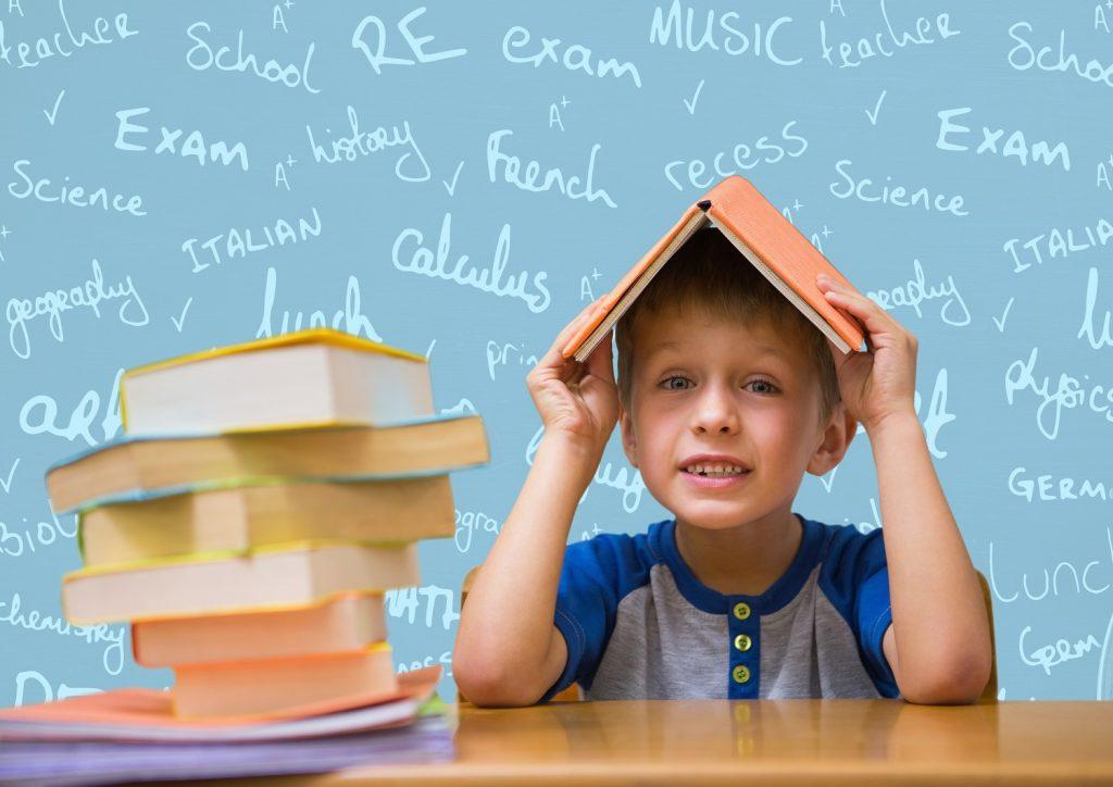 criança com um livro na cabeça, em frente a um quadro com palavras em inglês.