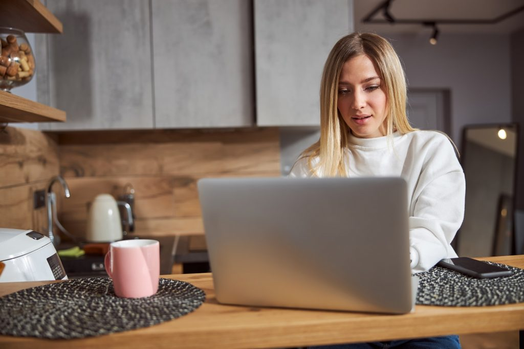 Woman is working at computer at home